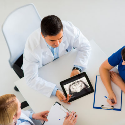 doctors-with-jaw-x-ray-on-tablet-pc-at-clinic-P4KUCAH_1